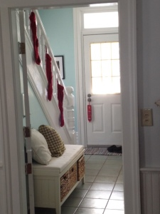 A hallway with three red stockings hung on a bannister.