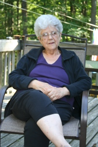 An older woman sits on a deck