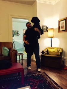 A man holding a giant black dog