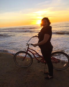 Pregnant woman standing bike with sunset in background