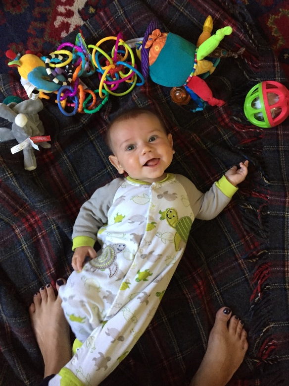 A baby on the ground, surrounded by toys and smiling