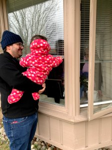 Florence and JF banging on vavo's window at the nursing home. Grandma is peaking out from inside.