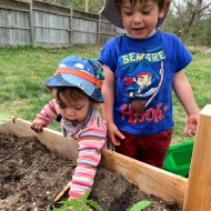 Both kids playing in the veggie box.